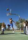 Man playing basketball on court while friends looking at him full length of young men Royalty Free Stock Photo