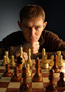Man playing chess sits at a chessboard with pieces Stock Image