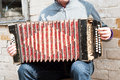 Man playing concertina with an old grunge near the brick wall Stock Images