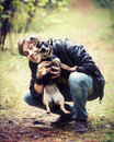 Man playing with dog a young his in a park Royalty Free Stock Photo