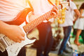 Man playing on electric guitar against band. Royalty Free Stock Photo