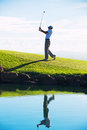 Man playing golf silhouette of on beautiful course reflection in water Royalty Free Stock Image