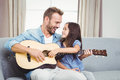 Man playing guitar with daughter at home Royalty Free Stock Photo