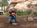Man playing guitar in a desert camp senior with cowboy hat on singing and while sitting on rock near red rock cliff the Royalty Free Stock Photos