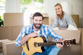 Man playing a guitar while woman unpackaging cardboard boxes in background Royalty Free Stock Photo