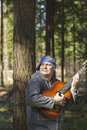 Man playing guitar in the woods Royalty Free Stock Photo