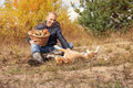 Man playing with his dog on autumn forest glade Royalty Free Stock Photo