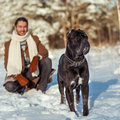 Man playing with his dog outdoors a in a winter forest cane corso Stock Photo
