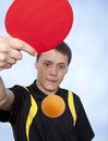 Man playing ping pong young against a blue background Royalty Free Stock Photos