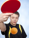 Man playing ping pong young against a blue background Stock Photos