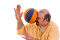Man playing sport being hit by a basket ball middle aged balding with goatee with force in the face when he misses catch or as Stock Image