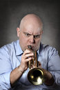 Man playing trumpet with focused expression deep grey background portrait Royalty Free Stock Photo