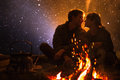 Man plays guitar and woman about the fire on the background of the starry sky Royalty Free Stock Photo