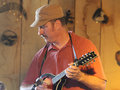 Man plays mandolin in a barn during a festival playing hobby instrument country music Royalty Free Stock Photo
