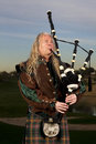 Man plays scottish bagpipes at dusk bagpipe music an arizona hotel resort golf course Stock Photo