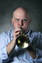 Man plays a trumpet looking into camera studio shot with grey background Royalty Free Stock Image
