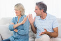 Man pleading with his wife after an argument at home on couch Stock Photo
