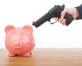 Man pointing a gun at a piggy bank Stock Images