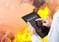 Man pointing at insurance wording on tablet with fire Royalty Free Stock Photo