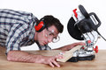 Man positioning plank of wood a in a mitre saw Royalty Free Stock Image