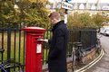 Man Posting Letter In Red British Postbox Royalty Free Stock Photo