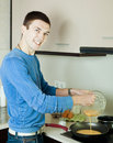 Man pouring dough in frying pan at home kitchen Royalty Free Stock Photos