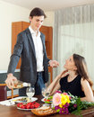 Man pours sparkling wine to a glass his young wife in home Royalty Free Stock Photography