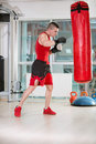Man practicing box young kicks with a punching bag at a gym Stock Photo