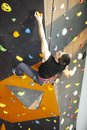 Man practicing rock climbing on rock wall indoors young a Royalty Free Stock Photos