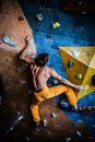 Man practicing rock climbing on a rock wall muscular indoors Royalty Free Stock Images