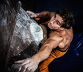 Man practicing rock climbing on a rock wall muscular indoors Royalty Free Stock Photos