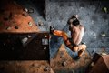 Man practicing rock climbing on a rock wall muscular indoors Stock Photos