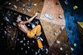 Man practicing rock climbing on a rock wall muscular indoors Royalty Free Stock Photography