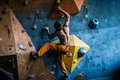 Man practicing rock climbing on a rock wall muscular indoors Stock Images