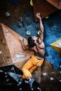 Man practicing rock climbing on a rock wall muscular indoors Royalty Free Stock Image