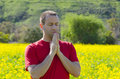 Man praying alone in a an open field in nature. Royalty Free Stock Photo