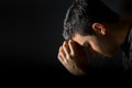 Man praying young in the dark Stock Photo