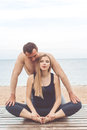 Man and pregnant girl are doing yoga at sea coast Royalty Free Stock Photo