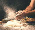 Man preparing bread dough on wooden table in a bakery Royalty Free Stock Photo