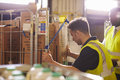 Man preparing roll cages for delivery, watched by supervisor Royalty Free Stock Photo