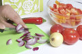 A man is preparing a vegetable salad. He cuts the onion on a cutting board. Royalty Free Stock Photo