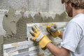 Man pressing an ornamental tile into a glue on a wall with gloved hands in diy concept Royalty Free Stock Photography