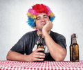Man in pub drunk with clown wig sitting the Royalty Free Stock Photo