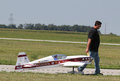 Man pulls model airplane radio controlled on landing strip at national aviation day event Stock Image