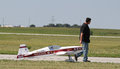 Man pulls red model airplane and white radio controlled on landing strip at national aviation day event Stock Photography