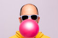 Man with purple sunglasses blowing pink chewing gum and facing the camera Royalty Free Stock Photo