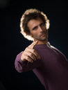 Man in purple sweater gestures pointing finger Royalty Free Stock Images