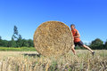 Man pushing hay bale Stock Photography