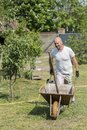 man pushing wheelbarrow. Young man pushing a wheelbarrow on the farm Royalty Free Stock Photo