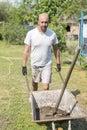 man pushing wheelbarrow. Young man pushing a wheelbarrow on the farm. Royalty Free Stock Photo